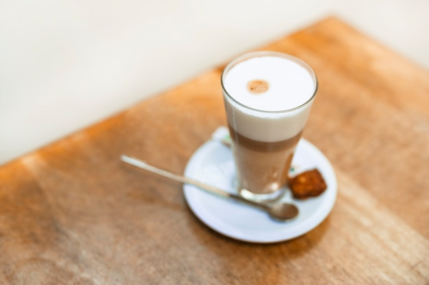An overhead view of cappuccino coffee in a transparent glass on table