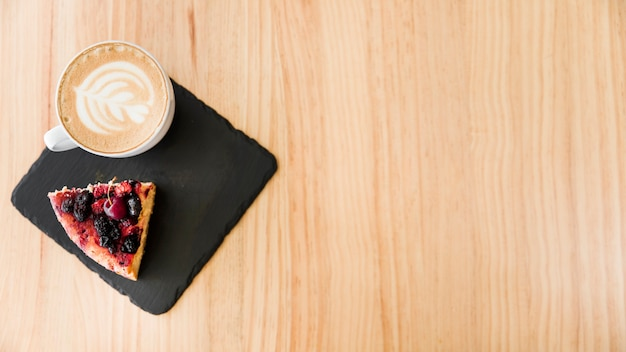 An overhead view of cappuccino coffee with art latte and cake slice on wooden backdrop