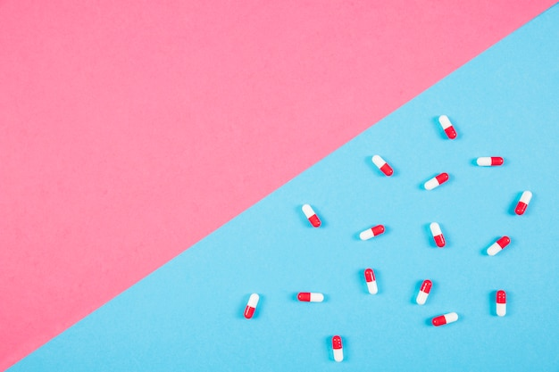 Overhead view of capsules on blue and pink background