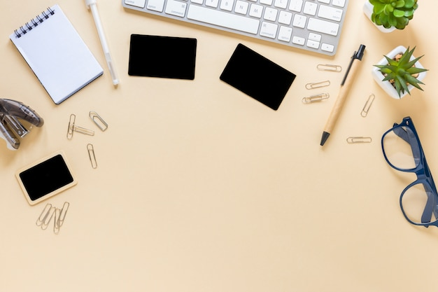 An overhead view of cards; spiral notepad; pen; eyeglasses and cactus plant with keyboard