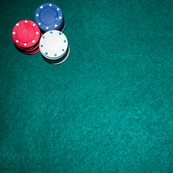 Overhead view of casino chips stack on green poker table