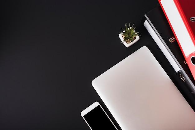 Una vista dall'alto del telefono cellulare; il computer portatile; pianta di cactus e file su sfondo nero