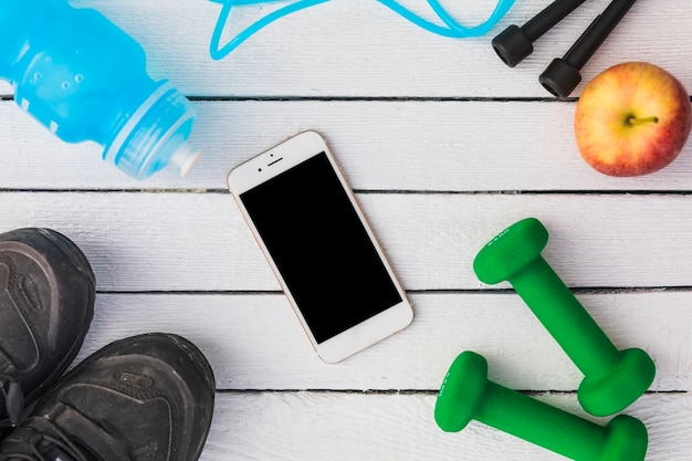 An overhead view of cellphone with bottle; skipping rope; apple; dumbbells; and shoes on wooden plank