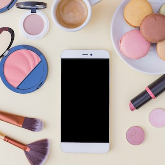 An overhead view of cellphone with cosmetics product and breakfast on beige background