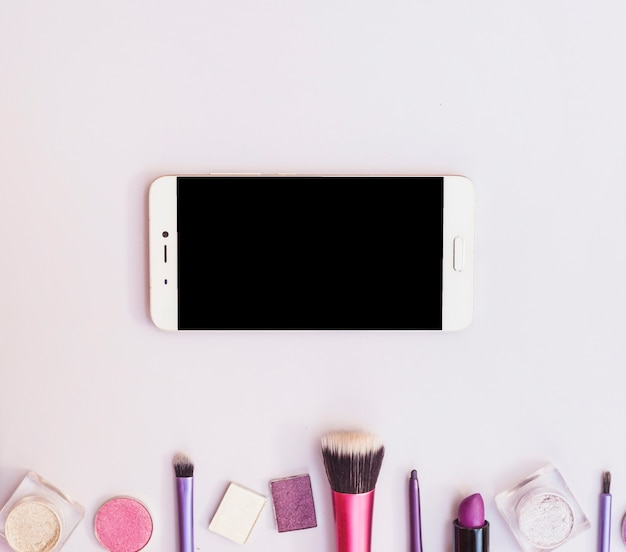 Overhead view of cellphone with cosmetics products on bottom of the background
