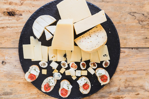 An overhead view of cheese blocks on black slate board on table