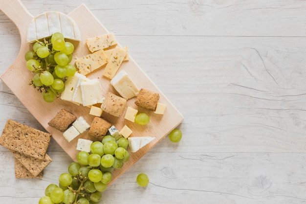 An overhead view of cheese blocks, crisp bread and grapes on wooden desk