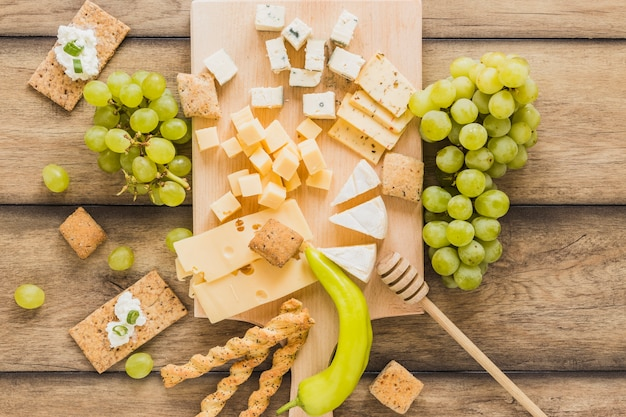 An overhead view of cheese blocks, grapes, crisp bread with cheese cream; green chili on wooden table