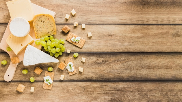 An overhead view of cheese blocks; grapes; crisp bread with cheese cream on wooden table