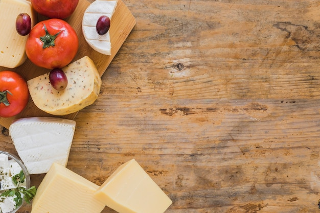 An overhead view of cheese blocks, grapes and tomatoes on wooden desk