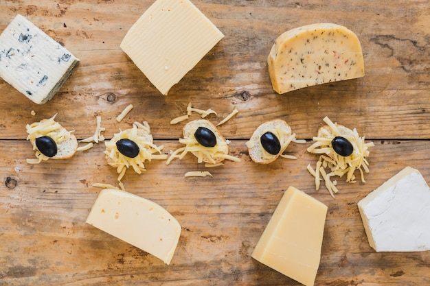 An overhead view of cheese blocks with mini sandwiches on wooden surface