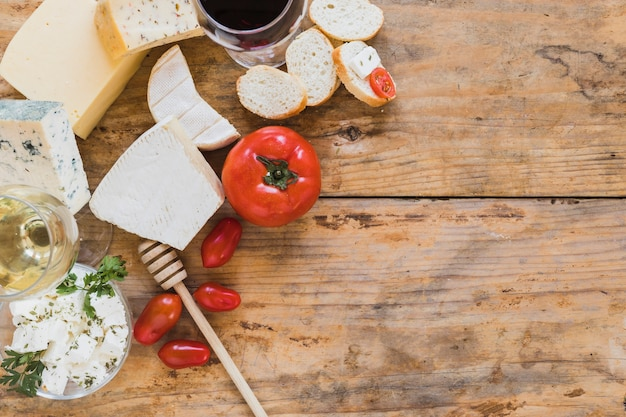 An overhead view of cheese blocks with tomatoes and bread on wooden backdrop