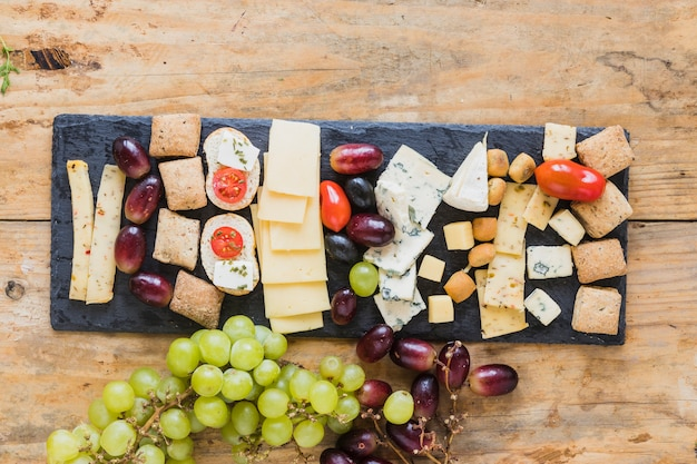 An overhead view of cheese, grapes and mini bread on slate board over the table