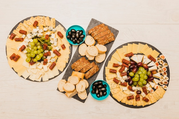 An overhead view of cheese platter with slices of bread and olives on wooden desk