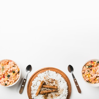 Overhead view of chinese fried and steam rice with cinnamon sticks on white surface
