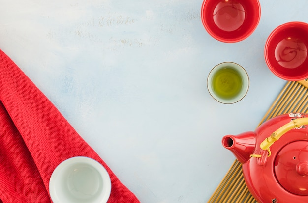 An overhead view of chinese teapot and teacups on white background