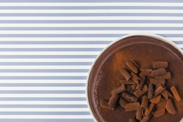 An overhead view of chocolate cake on stripes background