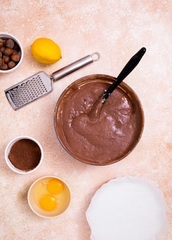 An overhead view of chocolate dough with ingredients on kitchen counter