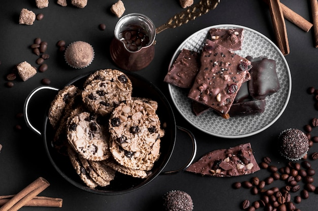 An overhead view of chocolate muesli cookies and chocolate on black background
