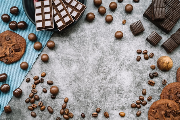 Overhead view of chocolate products with roasted coffee beans on grunge backdrop
