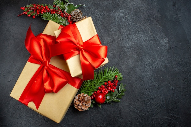 Overhead view of christmas mood with beautiful gifts with bow-shaped ribbon and fir branches decoration accessories on the right side on a dark background