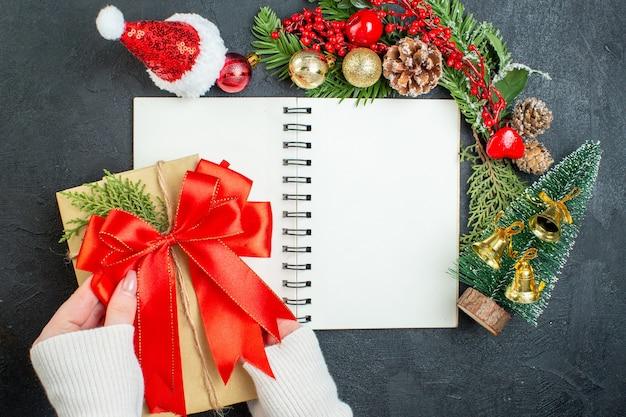 Vista dall'alto dell'umore natalizio con il nastro rosso dell'albero di natale del cappello del babbo natale dei rami dell'abete sul taccuino su fondo scuro