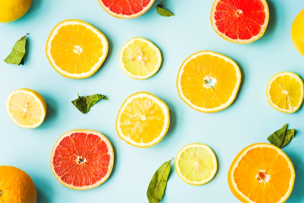 Overhead view of citrus fruit slices on blue background