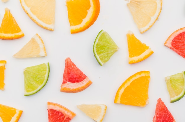 An overhead view of citrus fruit slices on white backdrop