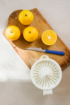 Overhead view of citrus fruits on chopping board