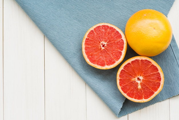 Overhead view of citrus fruits and cloth on wooden background