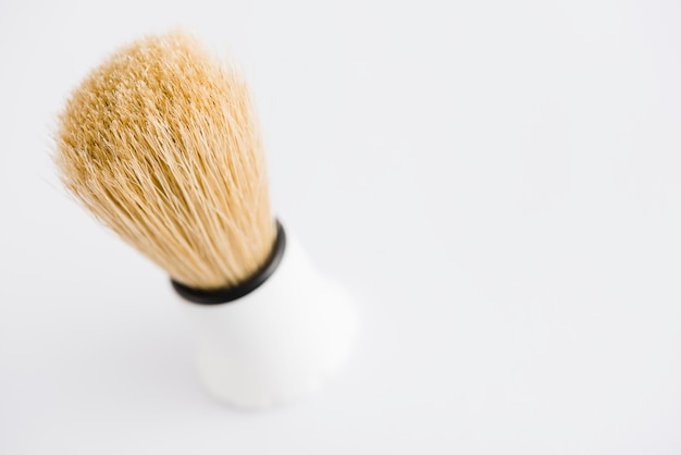 An overhead view of classic shaving brush against white background