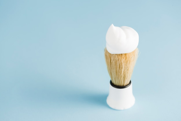 An overhead view of classic shaving brush with white foam against blue background