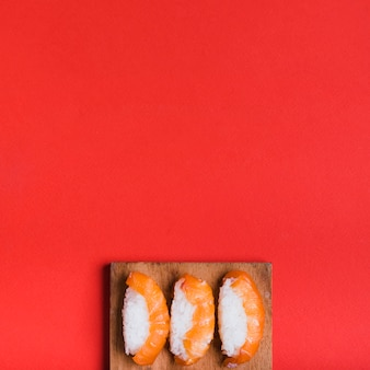 An overhead view of classic sushi with salmon on chopping board against red background