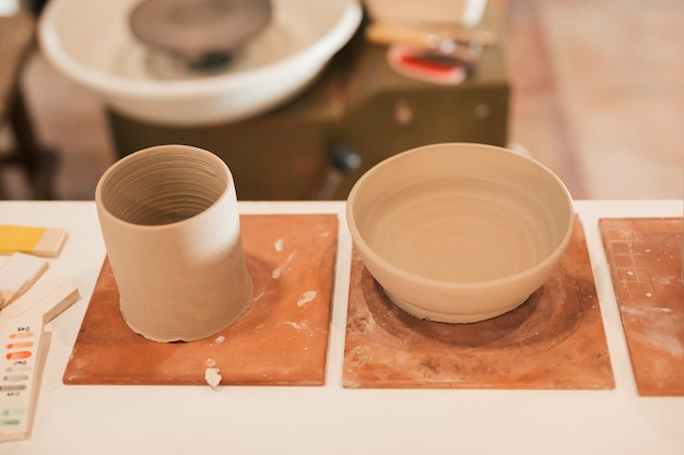 An overhead view of clay jar and bowl on table in workshop