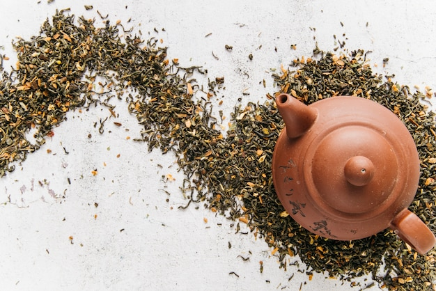 An overhead view of clay teapot on dry tea herbs over the concrete backdrop
