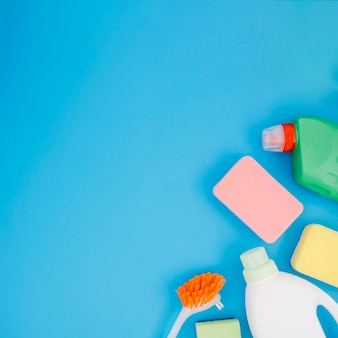 An overhead view of cleaning products on blue background