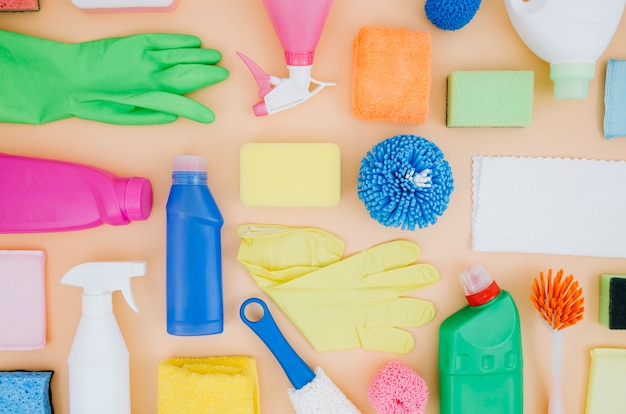 An overhead view of cleaning products still life on peach backdrop
