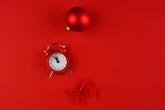 Overhead view of a clock and red christmas decoration on red paper background with copy space.