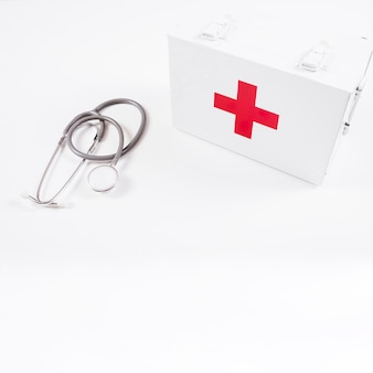 Overhead view of closed first aid kit and stethoscope on white background