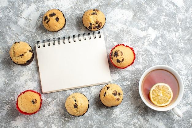 Vista dall'alto del taccuino chiuso tra deliziosi piccoli cupcakes con cioccolato e mano che tiene una tazza di tè nero con limone sulla superficie del ghiaccio