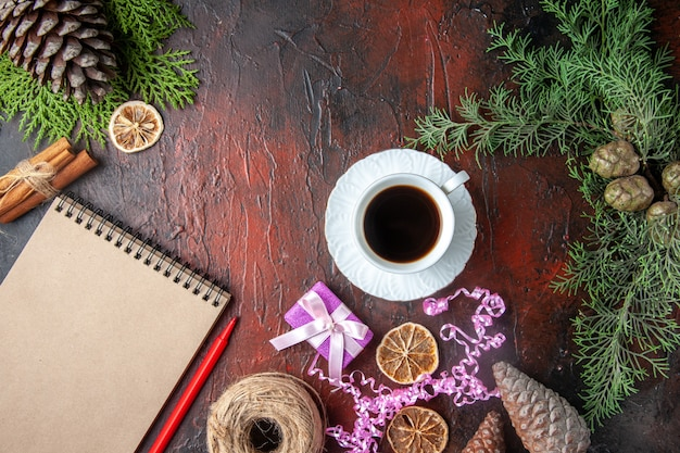 Overhead view of closed notebook with pen cinnamon limes and a ball of rope gift conifer cones on dark background