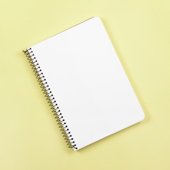 An overhead view of closed spiral notebook on yellow background