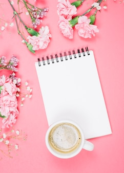 An overhead view of coffee cup on blank notepad with carnations; gypsophila; limonium flowers on pink background