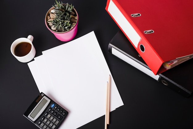 An overhead view of coffee cup; calculator; pot plant; blank white papers; pencils and paper files on black background
