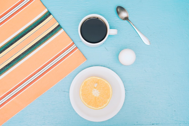 An overhead view of coffee cup; eggs; spoon and halved orange on blue backdrop