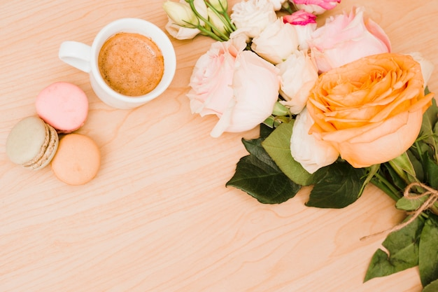 An overhead view of coffee cup; macaroons and flower bouquet on wooden background
