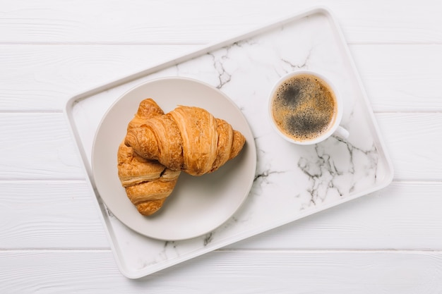 Overhead view of coffee cup and plate of croissant bread in tray