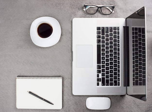 An overhead view of coffee cup; spiral notepad; pen; mouse; eyeglasses near an open laptop