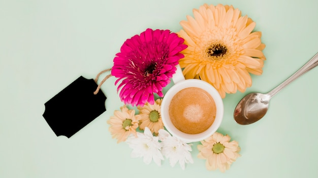 An overhead view of coffee cup with flower decoration and black blank tag on colored background