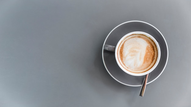 Overhead view of coffee latte on grey background